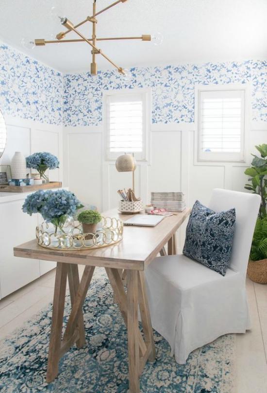 Home Office maritim einrichten interessante Raumgestaltung in Blau starke visuelle Wirkung leicht gemusterte Tapeten Teppich Deko Kissen blaue Hortensien in Vase