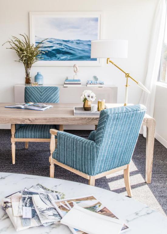 Home Office maritim einrichten sanfte Blautöne Wandbild Sessel viel natürliches Holz Gräser in Vase weiße Tischlampe