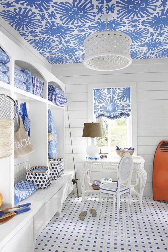 Home Office maritim einrichten weiß und blau in Kombination verspielte Muster an der Decke rechts Schrank vor dem Fenster Tisch Stuhl in Weiß Lampe