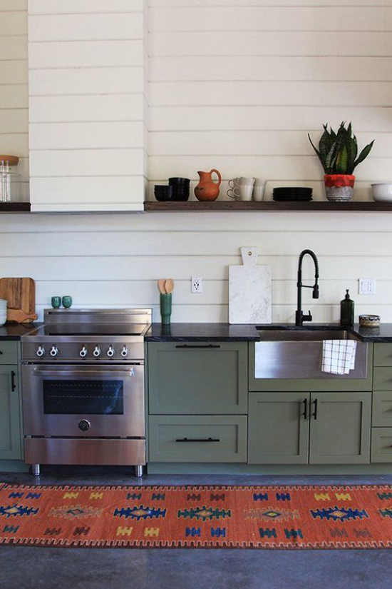 Küchenzeile im Retro Stil grüne Küchenschränke moderner Herd rustikaler Läufer gemustert