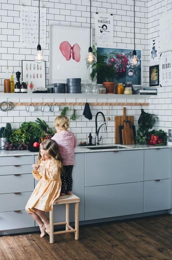 Küchenzeile im Retro Stil hellblaue Schränke zwei kleine Kinder Hocker Gemüse auf der Arbeitsplatte