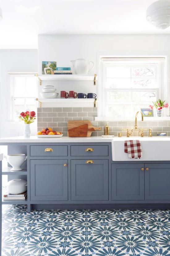 Küchenzeile in Retro Stil gemusterte Bodenfliesen in Blau Pastellblaue Unterschränke Fenster viel Licht bunte Farbtupfer Obst