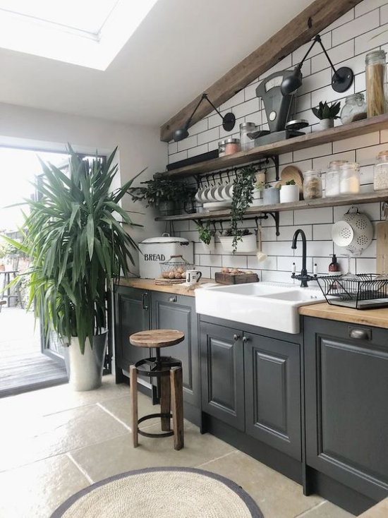 Küchenzeile interessantes Küchendesign helle und dunkle Farben üppige grüne Pflanze große Bodenfliesen