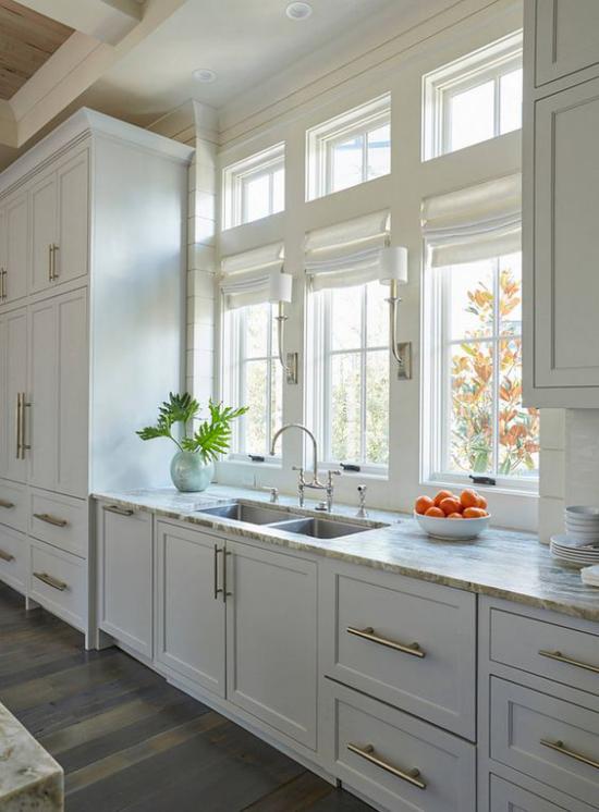 Küchenzeile klassisches Design aus Holz Ober-und Unterschränke am Fenster Spüle helle Farbe