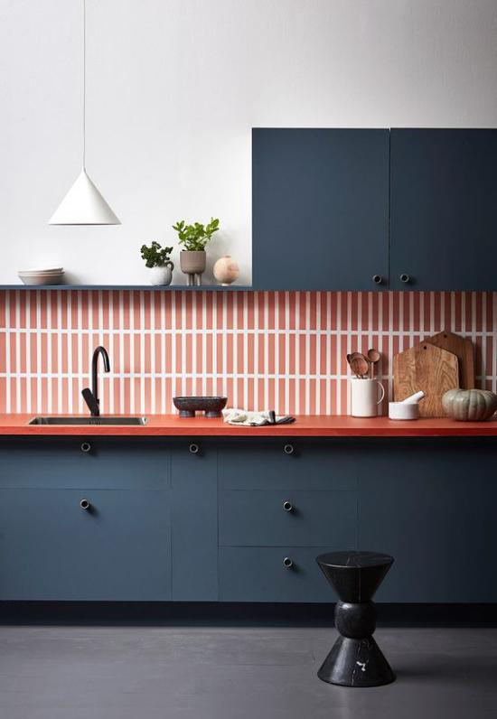 Küchenzeile moderne Ausführung straker Farbkontrast Dunkelblau Orange gestreifte Wandfliesen Holzbretter