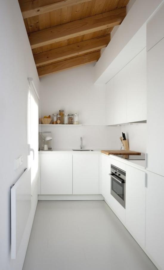 L-Küche ganz in Weiß unter der Dachschräge Holzbalken enger Raum Fenster links