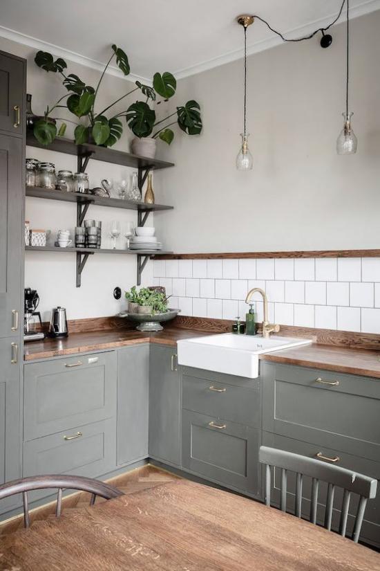 L-Küche in Retro Stil graue Unterschränke weiße Fliesen Küchenrückwand Holzregale grüne Topfpflanzen