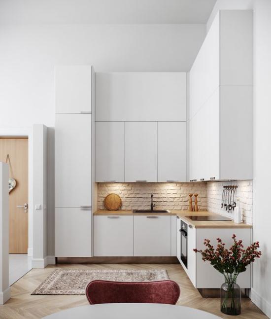 L-Küche kleine Ecke Ziegelwand gut beleuchtet sehr elegante weiße Küche Teil des offenen Wohnkonzeptes