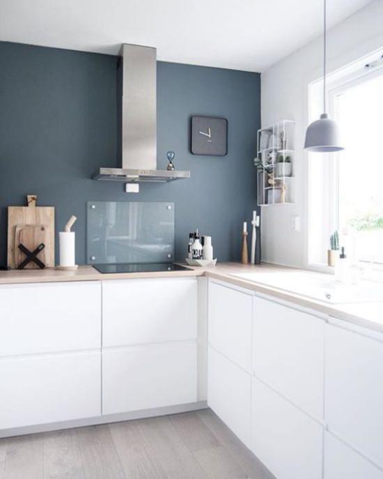 L-Küche weiße Unterschränke dunkelblaue Wand in Farbkontrast Dunstabzugshaube