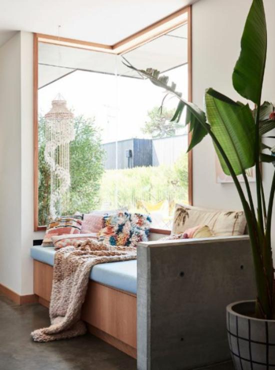 Platz am Eckfenster clever nutzen bequeme Couch Wurfdecke nachmittags ein Nickerchen machen