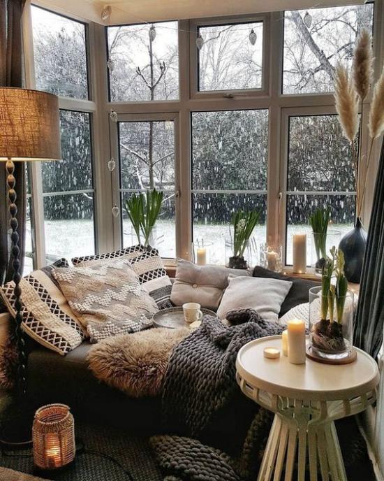 Platz am Eckfenster clever nutzen gemütliche Kuschelecke in Braunnuancen weiche warme Texturen Wolldecke Schaffell Kissen