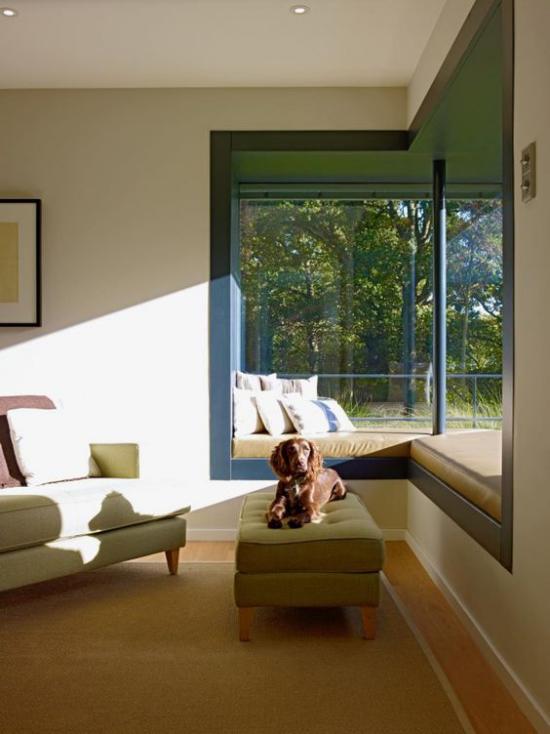 Platz am Eckfenster clever nutzen gepolsterte Ecksitzbank angenehme Raumatmosphäre Sonnenstrahlen Hund