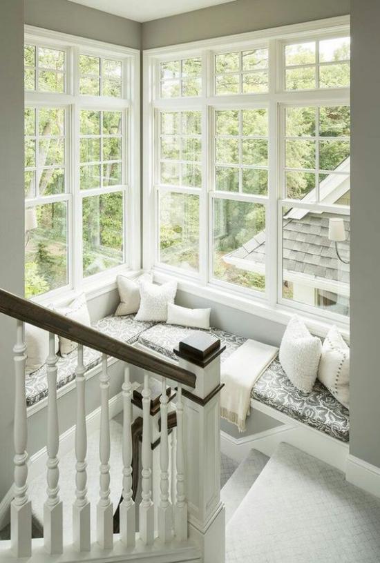 Platz am Eckfenster clever nutzen im Treppenhaus gemütliche Sitzecke einrichten in Weiß und Grau