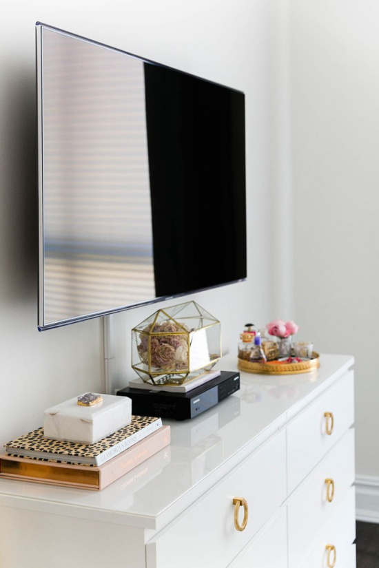 Router verstecken Fernseher an der Wand Kommode viele dekorative Gegenstände versteckter Router