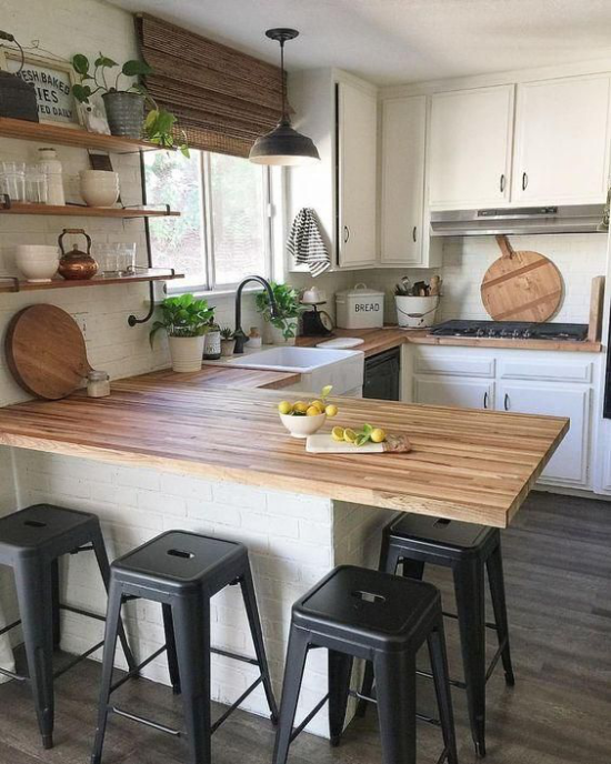 U-Küche Holzarbeitsplatten Hocker weiß getünchte Ziegelwand großes Fenster