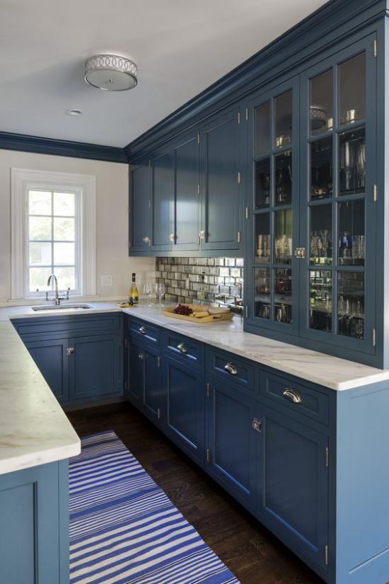 U-Küche dunkelblaue Küchenschränke gestreifter Läufer kleines Fenster weiße Arbeitsplatten