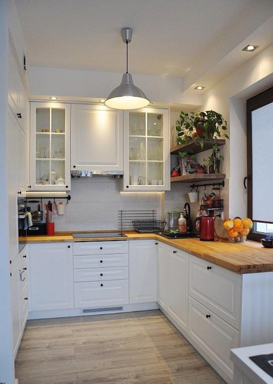 U-Küche eingebaute Beleuchtung Strahler Deckenleuchte weiße Unterschränke Holzarbeitsplatten Regale mit Topfpflanzen