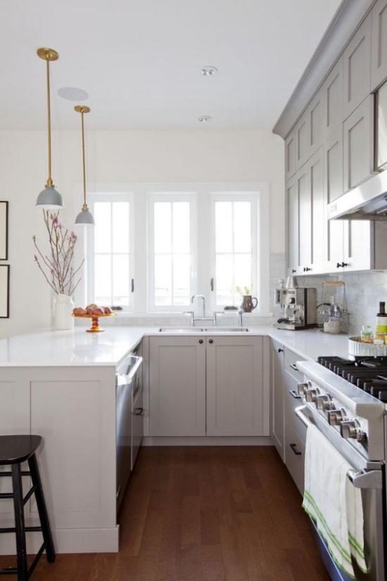 U-Küche ganz in Weiß Holzboden Fenster gute Ordnung Hängeleuchten über der Insel