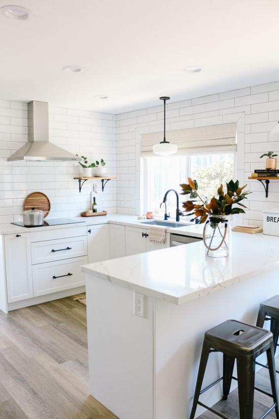 U-Küche heller gemütlicher Raum weiße Metro Fliesen viel Weiß Schränke Arbeitsplatten Hocker
