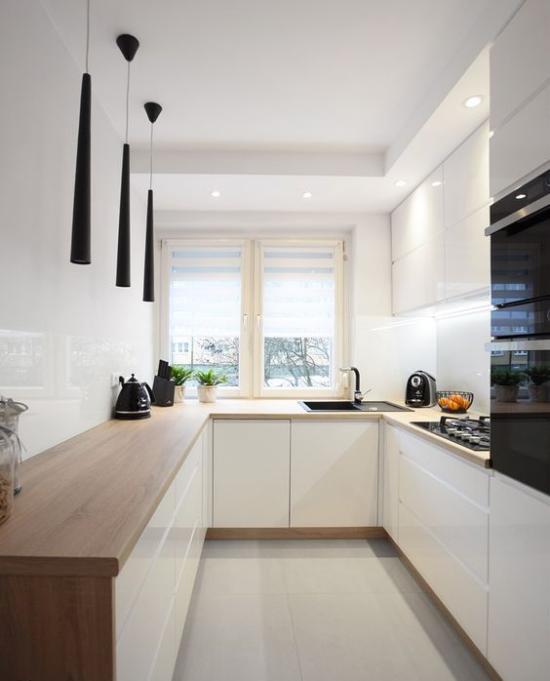 U-Küche perfektes Küchendesign Weiß dominiert drei Zeilen über Eck verbunden Hängelampen Strahler eingebaute Küchengeräte