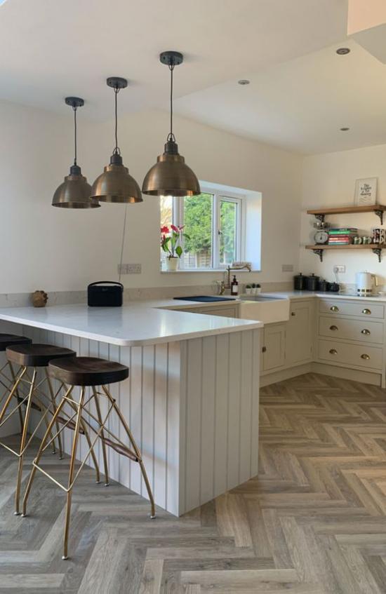 U-Küche stilvolles Küchendesign mit Retro Touches Hängeleuchten mit Metallglanz Hocker Parkettboden