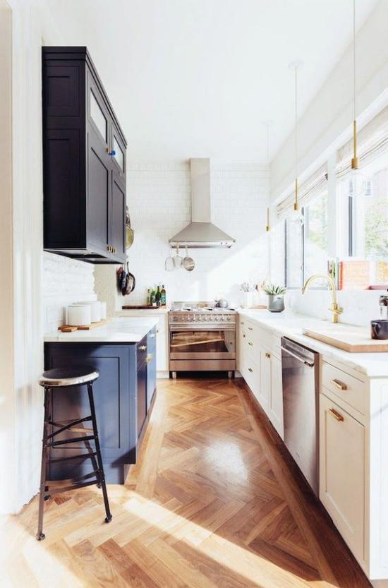 U-Küche weiße Fenster viel Tageslicht ansprechende Raumatmosphäre Schränke in Dunkelblau und Weiß Holzboden
