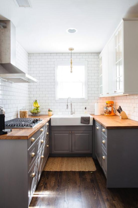 U-Küche weiße Metro Fliesen Holzboden Arbeitsplatten in warmer Holzfarbe