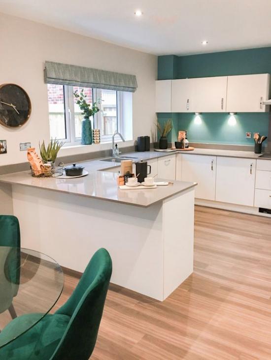 U-Küche weiße Schränke smaragdgrüne Wand schickes offenes Raumdesign Holzboden Fenster Wanduhr