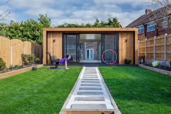 Yoga Garten anlegen und gestalten Sichtschutz große Gartenfläche viele grüne Pflanzen Rasen Steine Kies Zen Atmosphäre
