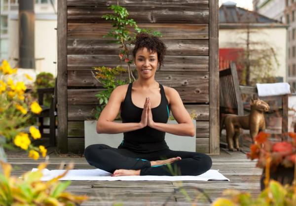 Yoga Garten anlegen und gestalten Yoga praktizieren junge Frau inmitten von viel Gartengrün ruhige Atmosphäre