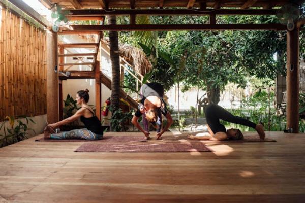 Yoga Garten anlegen und gestalten auf Holzplattform drei Yogis üben Sichtschutz Bambus