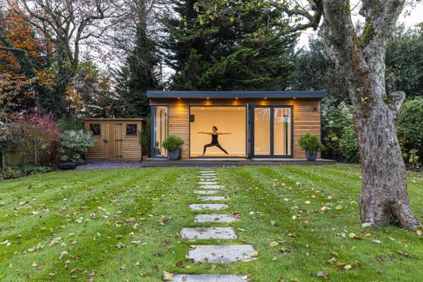 Yoga Garten anlegen und gestalten bei schlechtem Wetter junge Frau spielt Yoga im Gartenhaus