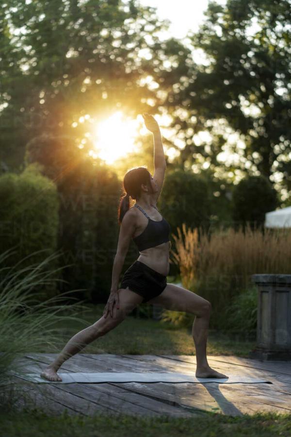 Yoga Garten anlegen und gestalten im Sonnenuntergang junge Frau Yoga Matte Übungen im Freien