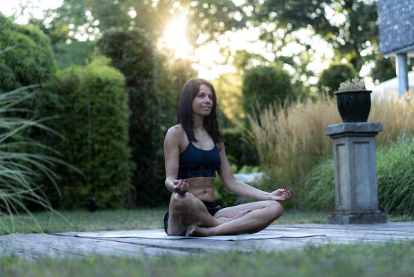 Yoga Garten anlegen und gestalten junge Frau bei Yoga Übungen und Meditation im Garten