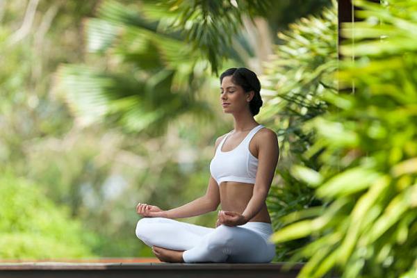 Yoga Garten anlegen und gestalten junge Frau bei Yoga-Praxis im Outdoor-Bereich