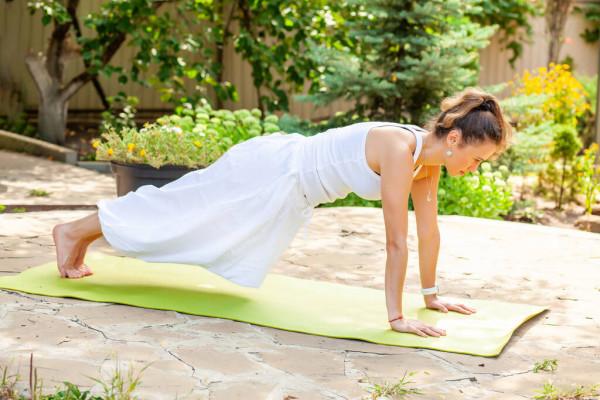 Yoga Garten anlegen und gestalten junge Frau praktiziert allein auf der Matte im Freien