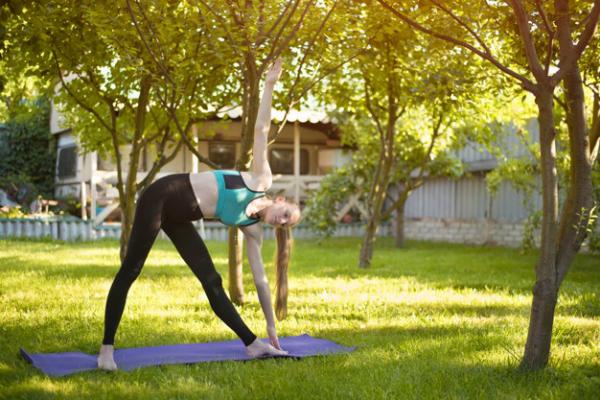 Yoga Garten anlegen und gestalten junges Mädchen macht Yoga Übungen im Schatten hoher Bäume im Freien