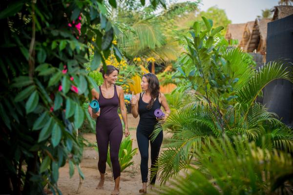 Yoga Garten anlegen und gestalten zwei junge Frauen sportliche Kleidung Yoga Matten tragen üppiges Grün ringsherum