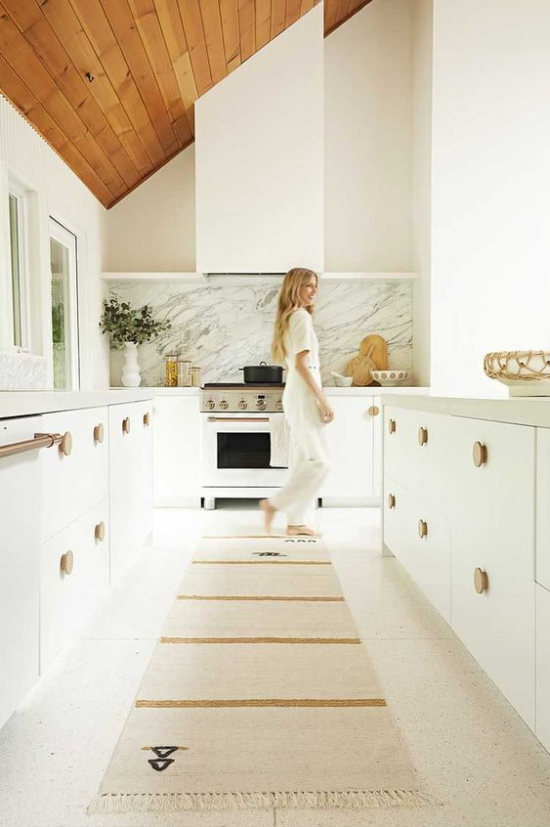 integrierte Dunstabzugshaube Eleganz im Küchendesign junge Frau weiße Küche Rückwand aus hellgrauem Marmor