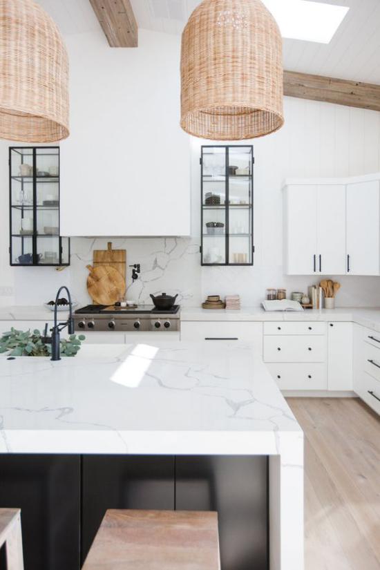 integrierte Dunstabzugshaube einladende Küche Hängelampen weiße Schränke schwarze Akzente Kücheninsel aus weißem Marmor