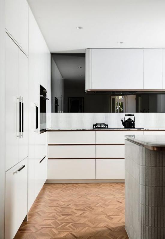 integrierte Dunstabzugshaube elegante weiße Küche kleine schwarze Akzente setzen