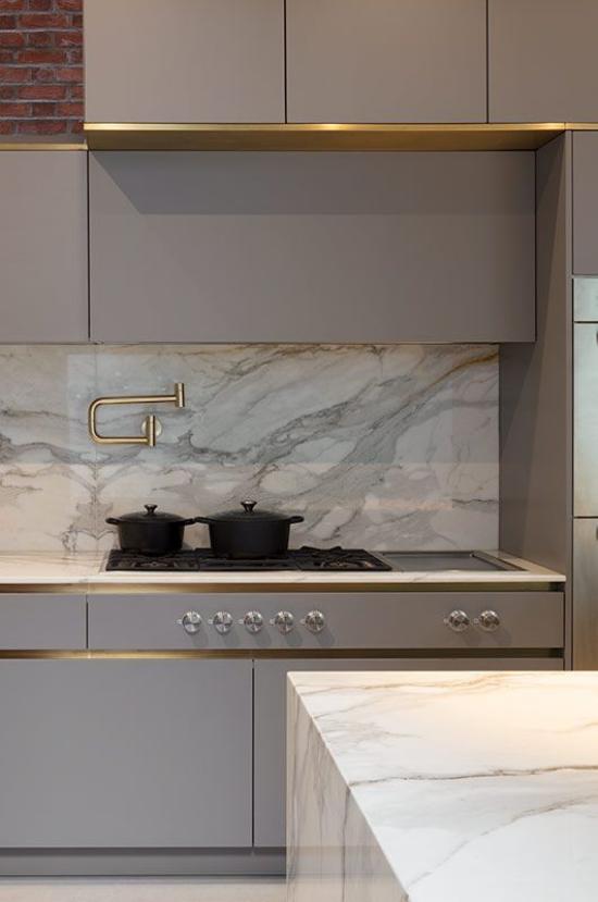 integrierte Dunstabzugshaube elegantes Küchendesign grauer Marmor kleine Goldakzente