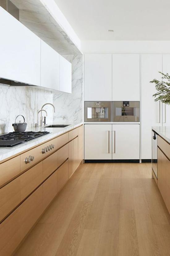 integrierte Dunstabzugshaube helles Holz Boden Unterschränke weiße Farbe dominiert Rückwand aus weißem Marmor
