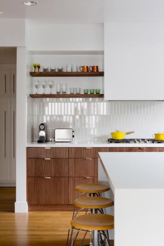 integrierte Dunstabzugshaube weiß dominiert Rückwand aus weißen Fliesen Schränke Kücheninsel