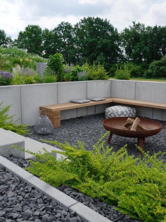 versunkener Sitzbereich im Freien Kieselstein Holztisch Bänke Betonzaun natürlicher Look