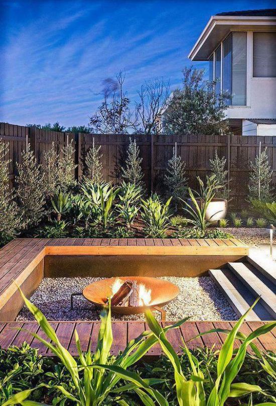 versunkener Sitzbereich im Freien Schutz der Privatsphäre Holzzaun viele grüne Pflanzen schöne Gestaltung auf viereckiger Fläche