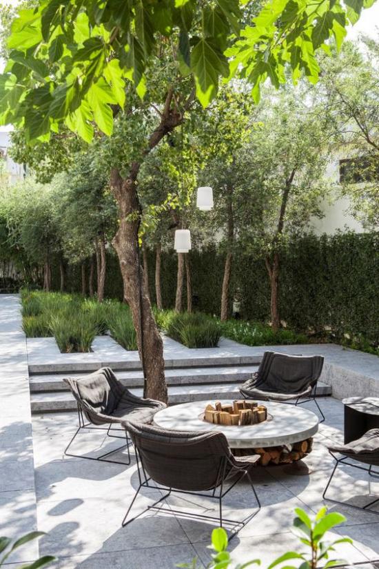 versunkener Sitzbereich im Freien Stein und Beton in der Mitte kleiner runder Tisch Stühle hoher Baum grüner Zaun