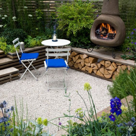 versunkener Sitzbereich im Freien auf kleiner Fläche Tisch zwei Stühle Kaminofen daneben Brennholz