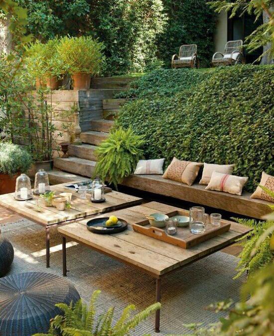 versunkener Sitzbereich im Freien einige Stufen tiefer gelegen ein grünes Paradies Holzbänke Holztische üppige Grünpflanzen
