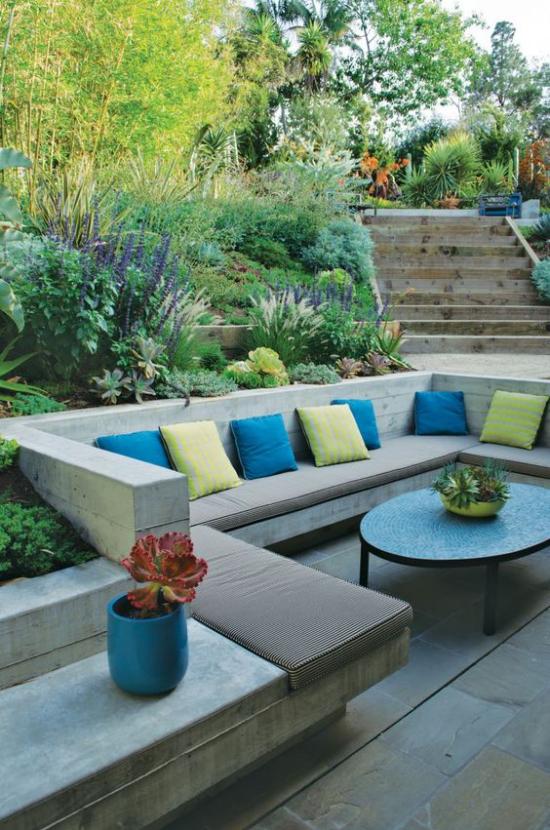versunkener Sitzbereich im Freien interessante Gestaltung einzelne Zonen abgetrennt gelbe und blaue Kissen Polsterung viele Grünpflanzen